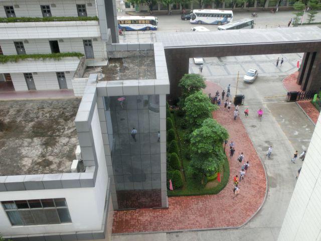 从1号教学楼上俯瞰大门,蓝色的大巴是校车,接送教师上下班